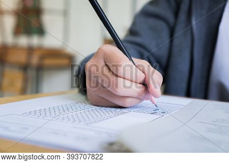 Hand Student Use Pencil Writing On Paper Optical Form Of Standardized Test Examination, Answer Sheet