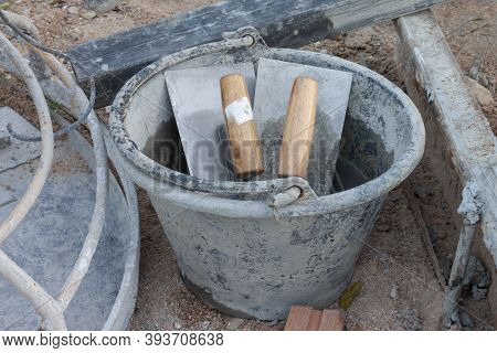 Plastering Trowel In Old Plastic Pail In Construction Site.