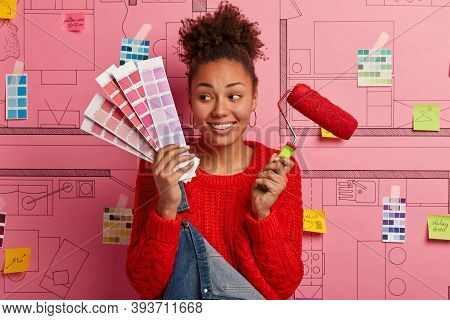 Cheerful Woman Holds Palette And Red Paint Roller, Looks Aside, Has Curly Combed Hair, Poses Against
