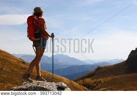 Tourist Girl With Walking Sticks Stands On The Top Of A Mountain And Admires The Beautiful Views Of