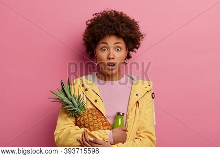 Stupefied Shocked Afro Woman Has Surprised Gaze At Camera, Holds Pineapple And Bottle Of Smoothie, R