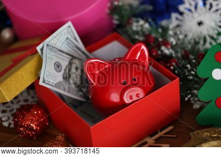 Piggy Bank With Money In Shape Of Pig In Gift Box Lying On Table Among Christmas Tree Decorations. F