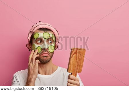 Shocked Bearded Man Looks With Embarrassement At Mirror, Applies Facial Clay Mask With Cucumbers, Ha