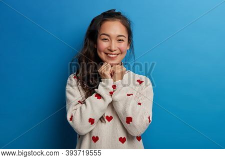 Portrait Of Dark Haired Mixed Race Brunette Woman Looks Gently At Camera, Keeps Both Hands Under Chi