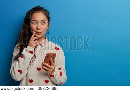Image Of Thoughtful Girl With Asian Appearance Browses Newsfeed Via Social Networks, Thinks Over Rec