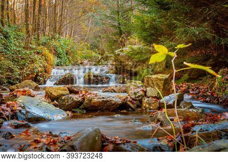 Autumn Forest And River Scene With Waterfall. Long Exposure. Seasonal Vibes And Warm Atmosphere. Bea