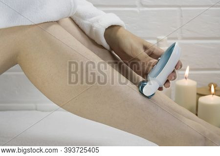 Epilation Of Legs At Home. Young Woman Shaving Her Legs Using An Electric Epilator. Woman Epilate Le