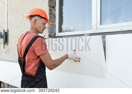 Insulation Of The House With Polyfoam. The Worker Is Installing A Styrofoam Board On The Facade.