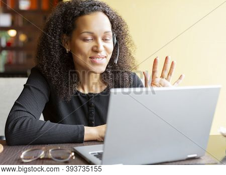 African American Woman Making Online Video Call Via Laptop Application. She Says Hi And Waves Her Ha