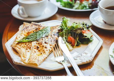 Fresh Baked French Savory Crepes Served With Greens On The Table With Cutleries