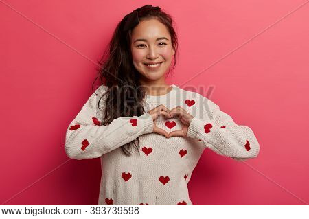 You Found Key To My Heart. Beautiful Smiling Korean Woman Makes Love Sign, Expresses Tender Feelings