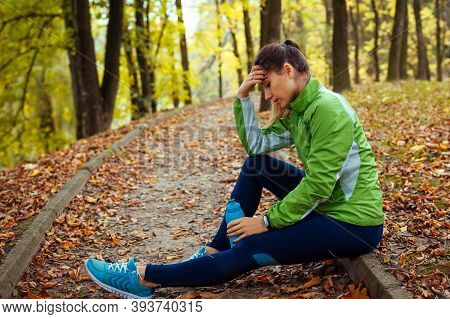 Exhausted Runner Having Rest After Workout In Autumn Park. Tired Woman Holding Water Bottle. Sportiv