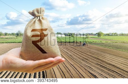 Hand Holds Out A Indian Rupee A Farm Field. Financial Support, Subsidies For Agriculture. Farm Loans