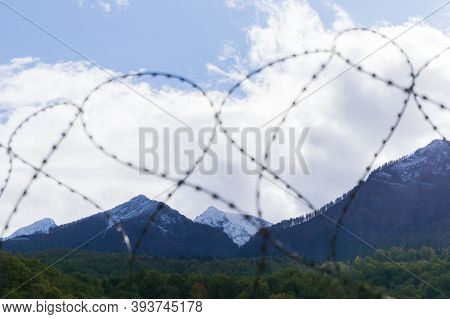 Barbed Wire On A Background Of Mountains. The Border Is Protected By Barbed Wire. Mountains And Barb