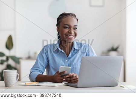 Self-employment. Joyful Black Millennial Woman Sitting At Workplace In Home Office, Enjoying Remote