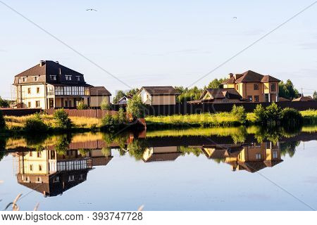 Country Houses On The Lake Behind The Trees, The Reflection Of Houses In The Water, A Windless Day