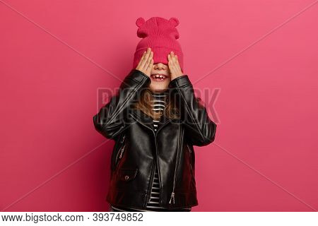 Joyous Girl Hides Face With Hat, Holds Palms On Eyes, Wears Fashionable Leather Jacket, Isolated On