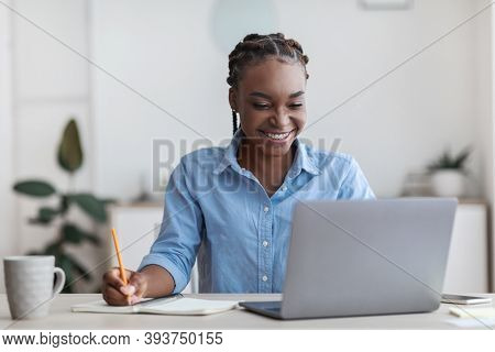 Online Education. Young Black Female Student Using Laptop At Home And Taking Notes, Smiling African