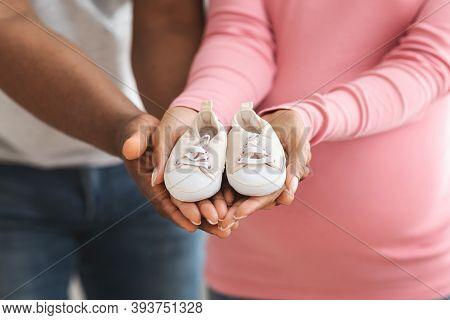 Parenthood Concept. Closeup Of Cute Baby Shoes In Pregnant Black Couple Hands. Unrecognizable Africa