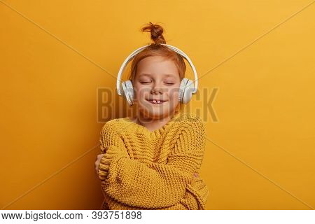 Joyful Redhead Girl With Hair Bun, Embraces Herself, Feels Comfort In New Knitted Sweater, Listens M