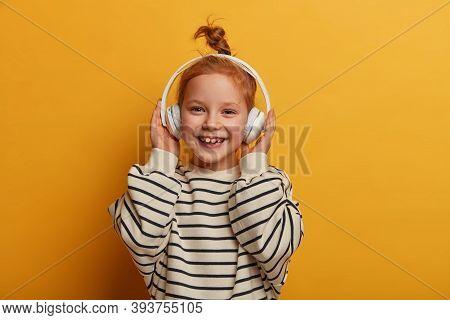 Positive Redhead Girl Enjoys Favorite Tune, Listens Music In Headphones, Has Optimistic Mood, Hair K