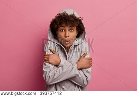 Horizontal Shot Of Shocked Young Afro American Woman Crosses Arms, Wears Anorak With Hoody, Feels Fr
