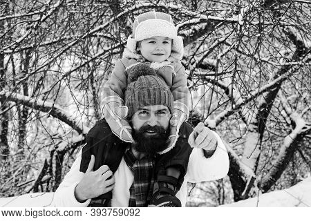 Father Giving Son Ride On Back In Park. Cute Son Hugs His Dad On Winter Holiday. Best Winter Game Fo
