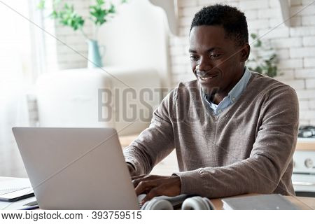 Smiling Professional Black Business Man Using Laptop Computer Working From Home Office. Happy Africa