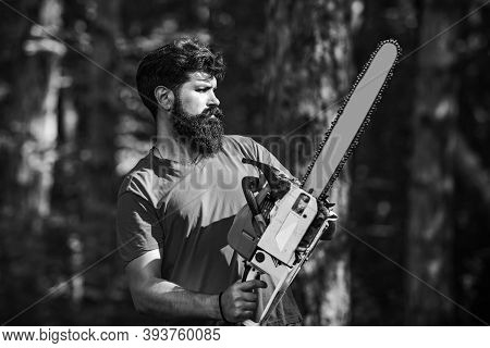 Woodcutter With Chainsaw On Sawmill. Woodworkers Lumberjack. Man Doing Mans Job. Woodcutter With Axe
