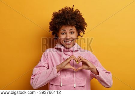 Body Language And Affection Concept. Lovely Caring Woman Shapes Heart Gesture, Smiles Positively, Co