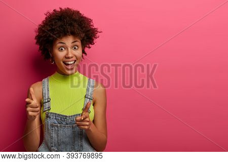 Joyful Ethnic Woman Points Both Index Fingers Gun Pistols, Laughs Happily, Chooses You, Dressed In D