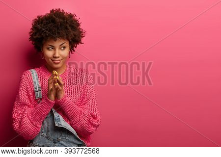 Cunning Young Afro American Woman Steepls Fingers, Looks Aside, Has Intention Or Tricky Plan, Wears