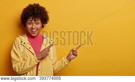 Cheerful Afro American Woman Points Right And Gives Good Recommendation, Wears Casual Anorak, Smiles