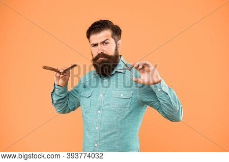 Barber As Ordered. Barber Ready To Shave Beard. Bearded Man Hold Barber Tools Beige Background. Trim