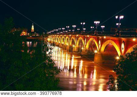Bordeaux Pont De Pierre In The Night . Garonne River And Illuminated Bridge De Pierre In Bordeaux