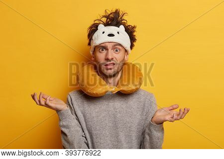 Confused Man Traveller Has Messy Hairstyle, Wears Blindfold And Travel Pillow, Spreads Palms Sideway