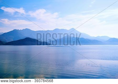 Twilight Over The Calm Lake Water And Island With Mountains. Famous Skadar Lake In Montenegro. Natur