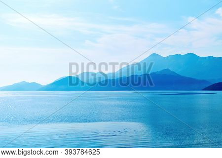 Calm Tranquil Skadar Lake And Mountains In The Fog And Sunlight. Morning Fog Over The Water Surface