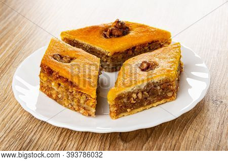 Three Pieces Of Baklava With Walnut In Glass White Plate On Wooden Table