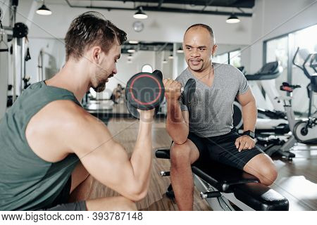 Mature Middle-aged Man Looking At His Coach Doing Biceps Exercise With Dumbbell And Repeating After