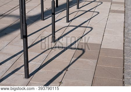 A Paved Sidewalk In A City With Bicycle Racks Casting Shadows In Sunlight