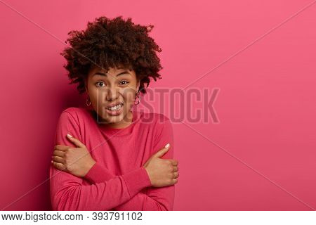 Indoor View Of Black Woman Crosses Hands Over Chest, Feels Cold After Walking During Frosty Weather,