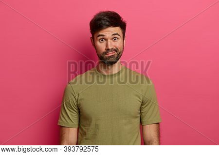Indignant Bearded Caucasian Man Purses Lips, Looks With Wonder, Sees Something Interesting, Wears Ca