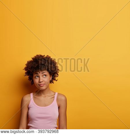 Vertical Shot Of Pensive Curly Millennial Girl Looks Thoughtfully Above, Dressed Casually, Sees Some