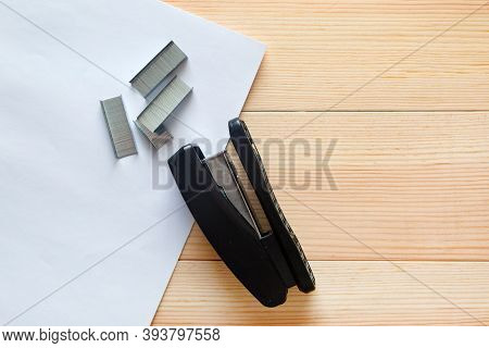 Stapler And Staples With Sheets Of Paper On A Wooden Table.
