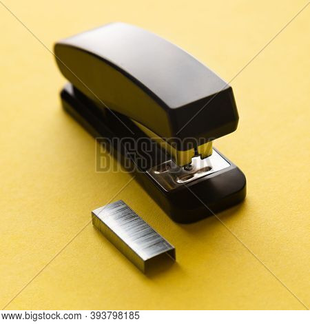 A Set Of Office Supplies. Stapler And Staples On Yellow Background.