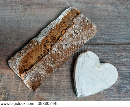 A French Neufchatel Cheese Shaped Heart On Wooden Background