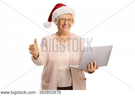 Happy elderly woman holding a laptop computer wearing a santa hat and showing thumbs up isolated on white background