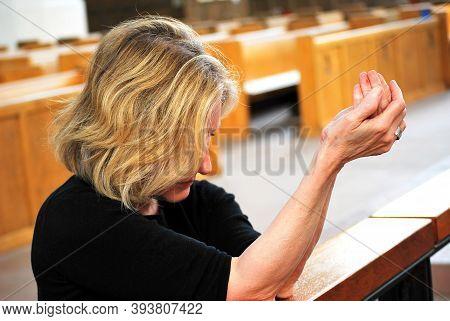 Mature Female Blond Beauty Praying Inside A Place Of Worship.