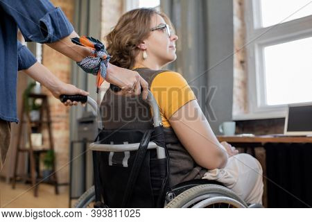 Hands of young woman pushing wheelchair with her disable sister or friend while taking care of her and helping to move around the house